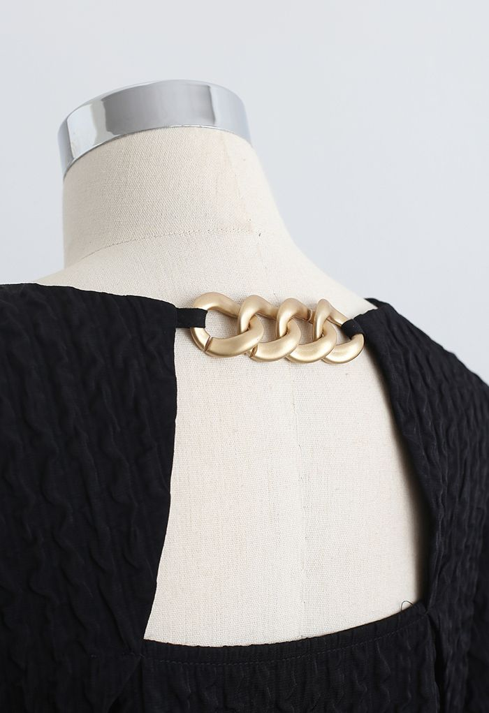 Mini-robe dorée en relief avec détail de chaîne en noir