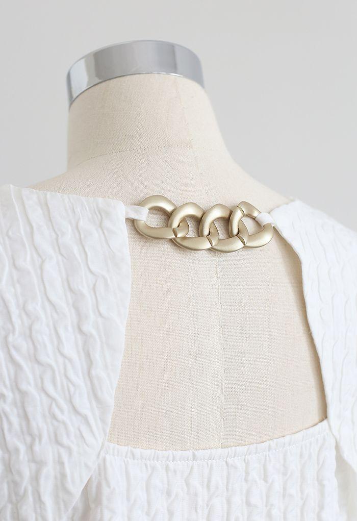 Mini-robe dorée en relief avec détail de chaîne en blanc