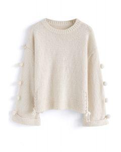 Pull en tricot pompon et signal de réchauffement en crème